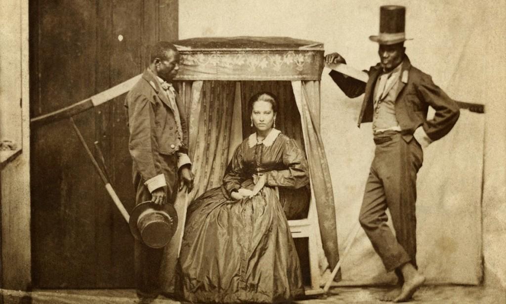 """Senhora na liteira (uma espécie de """"cadeira portátil"""") com dois escravos, Bahia, 1860 (Acervo Instituto Moreira Salles)."""