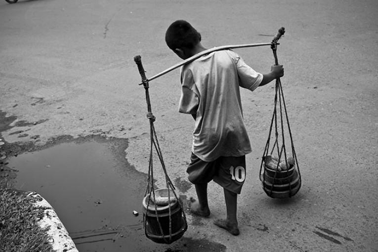 Um menino na Indonésia carrega instrumentos tradicionais usados para cozinhar. No mundo, 168 milhões de jovens estão submetidos ao trabalho infantil. Fotografia: Henri Ismail/Flickr