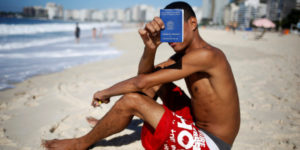 Brazilian unemployed Samuel Matias, 24, shows his Work and Social Security (CTPS) document on Copacabana beach in Rio de Janeiro, Brazil, May 2, 2016. REUTERS/Nacho Doce